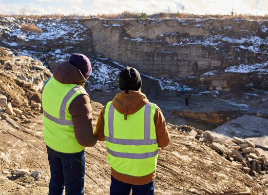 Back view portrait of two industrial workers wearing reflective jackets, one of them African, standing on cliff overlooking mineral mines on worksite outdoors, copy space